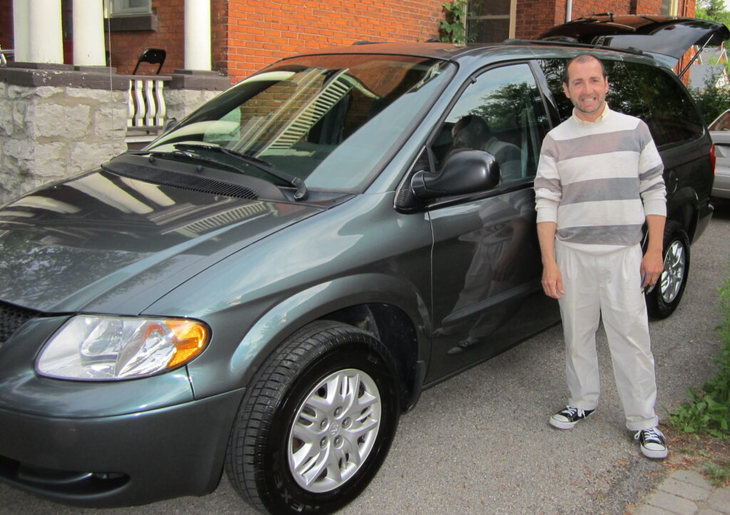 Man in a striped sweater standing beside a grey minivan and smiling.