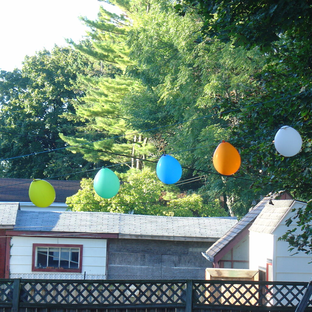 Balloons hanging on a clothesline with trees and garages in the background.