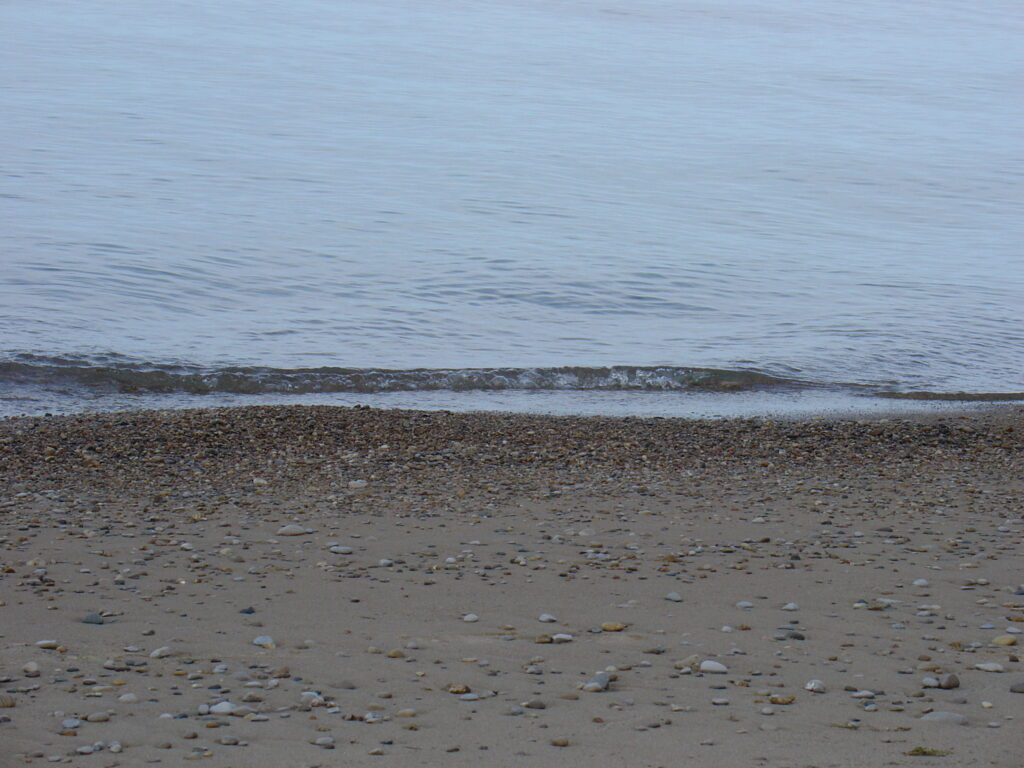A beach with a small wave rolling in. There are lots of stones on the beach.